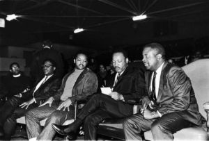 """Reverends Jesse Jackson and Ralph Abernathy on opposite sides of MLK, who appears to making notes for the speech that he will be delivering. This final speech is widely known today as King's """"Mountaintop"""" speech."""